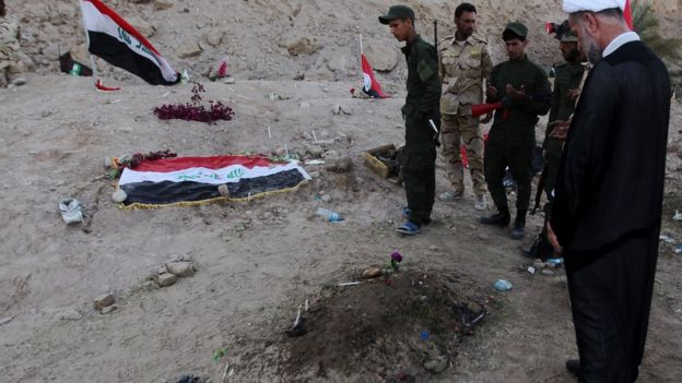 Iraqi Shia fighters examine a burial site thought to hold victims of the Camp Speicher massacre