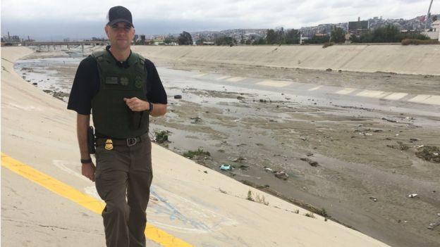 Border patrol agent Shawn Moran stands at the US-Mexico border
