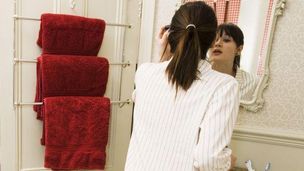 Mujer frente al espejo en el baño, junto a un barral con tres toallas colgadas
