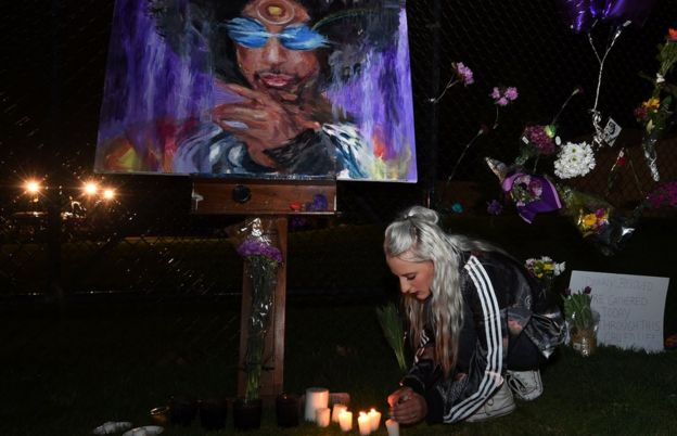 Fans light candles outside the Paisley Park residential compound of music legend Prince in Minneapolis, Minnesota, on April 21, 2016
