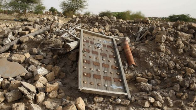 A door from a mausoleum lies on a pile of rubble in Timbuktu