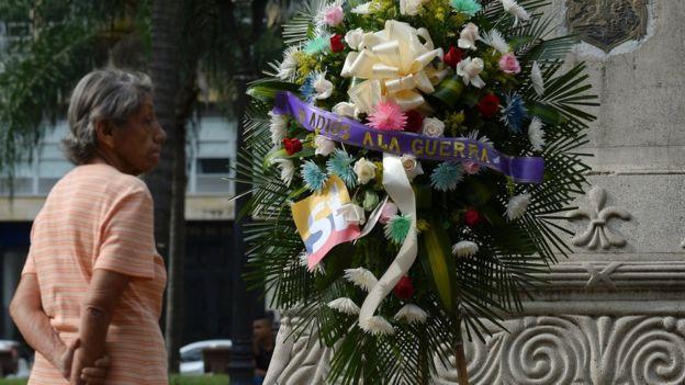 Una corona de flores con el mensaje adiós a la guerra.