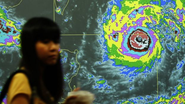 A Taiwanese walks past a video screen with the graph of Typhoon Nepartak heading towards Taiwan
