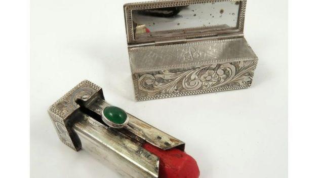 A silver lipstick case and red lipstick