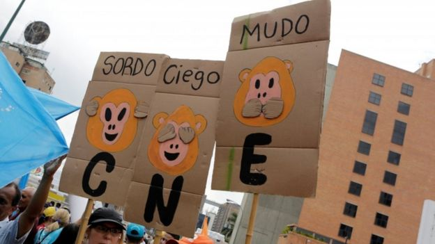Opposition supporters hold placards during a rally to demand a referendum to remove President Nicolas Maduro in Caracas, Venezuela, May 14, 2016. The placards (L-R) read