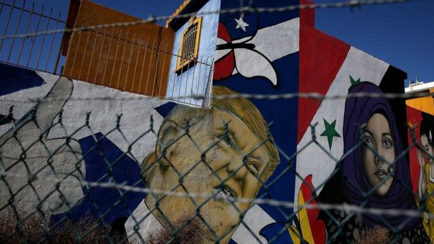 Un mural muestra al presidente Donald Trump junto a una joven con el cabello cubierto junto a la bandera de Siria en Tijuana, México