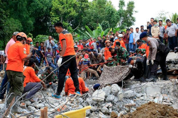 Indonesian army and the Search and Rescue Team look for survivors amongst the rubble on 7 December 2016 in Lueng Putu town, Aceh Province, Indonesia