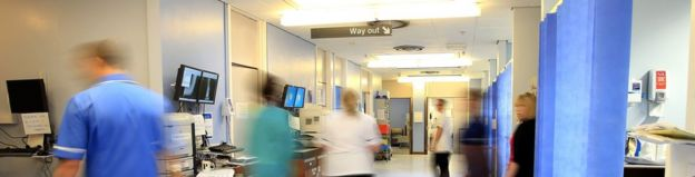 File photo from 2014 showing staff walking around a hospital ward corridor.