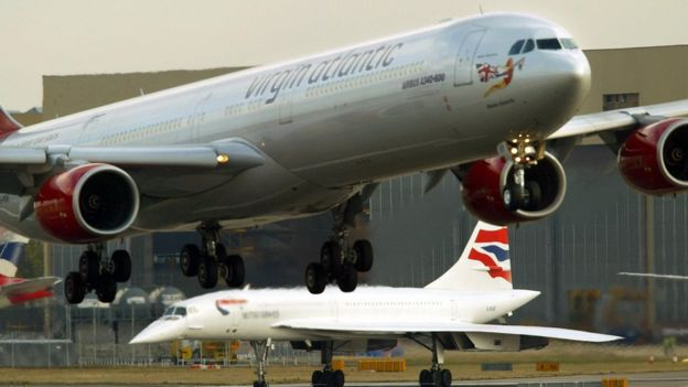 A Concorde waits to take off as a Virgin Atlantic jet comes in to land at London Heathrow airport 24 October 2003.