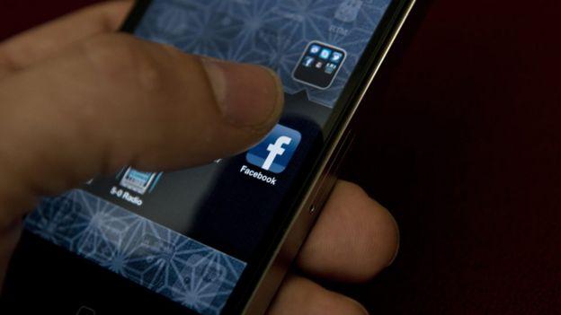 Alguien a punto de abrir la aplicación de Facebook en su celular.