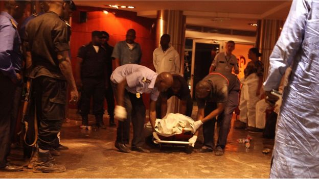 Mali security personal pick up the lifeless body of a victim inside the Radisson Blu hotel after an attack by gunmen on the hotel in Bamako, Mali, Friday, Nov. 20, 2015