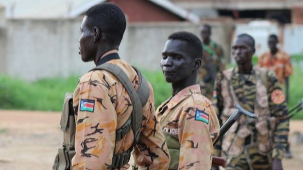 South Sudanese policemen and soldiers stand guard along a street following renewed fighting in South Sudan
