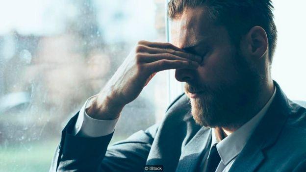 Un hombre apretándose los párpados, en señal de cansancio
