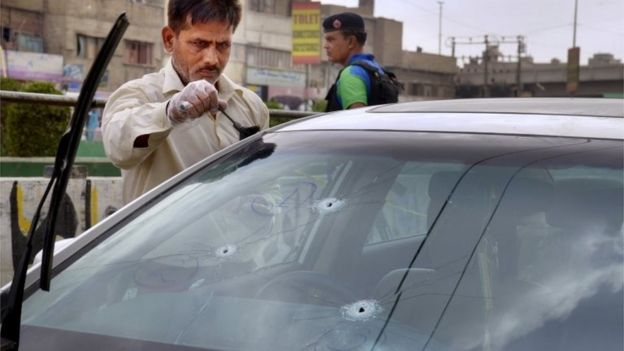 A forensic expert collects evidence from the car of famous Sufi singer Amjad Sabri after an attack in Karachi, Pakistan, Wednesday, June 22, 2016.