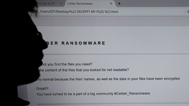 An IT researchers stands next to a giant screen a computer infected by a ransomware