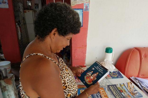 Sandra Maria de Andrade sostiene un libro.