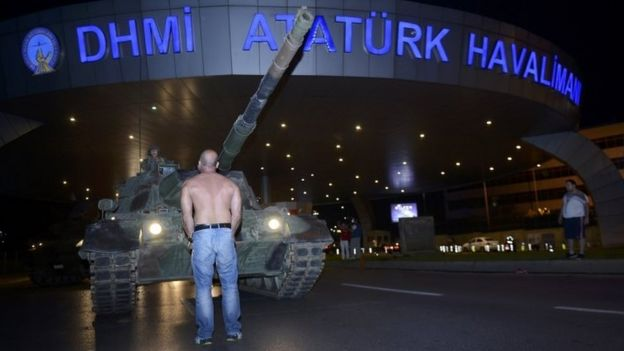 A man stands in front of a Turkish army tank at Istanbul's Ataturk airport.