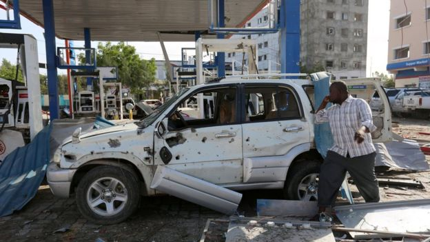 A man looks at the wreckage of his car destroyed at a petrol station during an in Mogadishu on 26 June