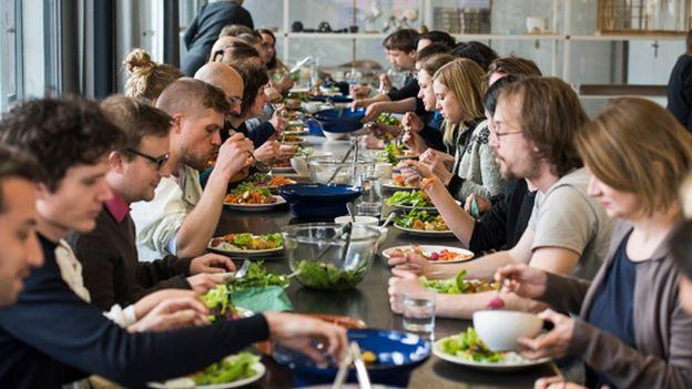 Grupo de personas sentadas comiendo vegetales.