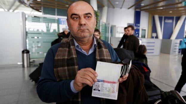 Fuad Sharef Suleman mostra seu passaporte à imprensa no aeroporto de Erbil, no Iraque