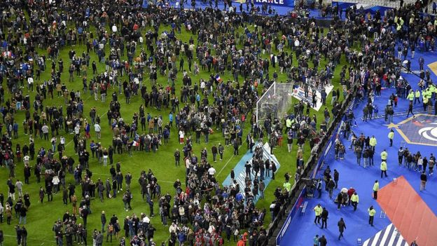 Football fans gather on the field of the Stade de France stadium after explosions during a friendly football match between France and Germany in Saint-Denis, north of Paris, on 13 November 2015 - one of a number of deadly attacks on the night