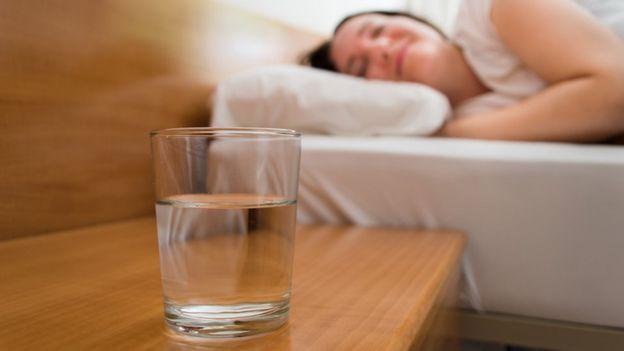 Persona durmiendo con vaso de agua