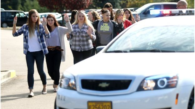Students, staff and faculty are evacuated from Umpqua Community College in Roseburg, Ore. on 1 October 2015, after a deadly shooting.