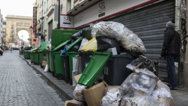 Un hombre camina junto a contenedores llenos de basura.