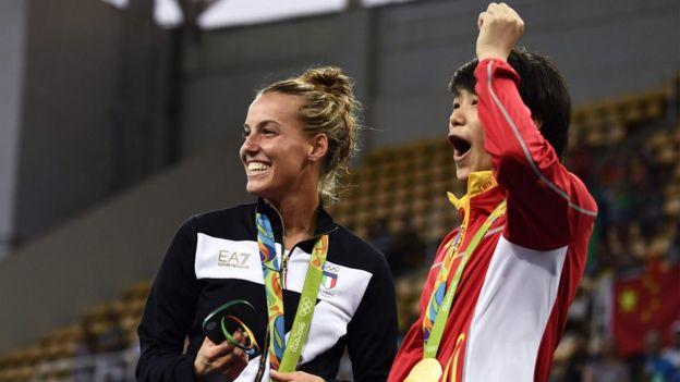 Shi Tingmao (dir.), que ficou com o ouro, e Tania Cagnotto, que ganhou o bronze, comemoram o pedido