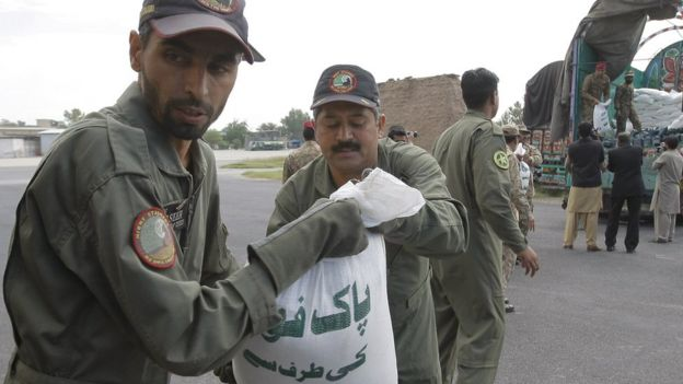 Pakistani soldiers load relief goods to a plane for earthquake victims, in Peshawar, Pakistan, Tuesday, Oct. 27, 2015.