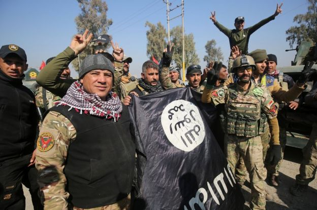 Iraqi soldiers flash victory signs and brandish an IS flag after entering Mosul airport, 23 February