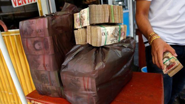 Una persona con una paca de dinero en bolsas
