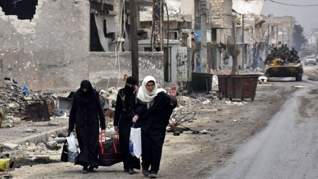 Personas caminan por las calles destruidas de Alepo.