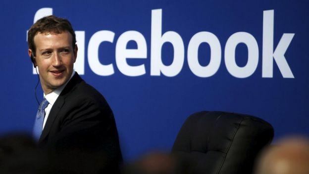 Mark Zuckerberg usando traje y de pie delante de la palabra