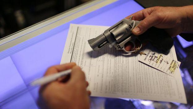Un vendedor rellena una planilla para la venta de un arma.