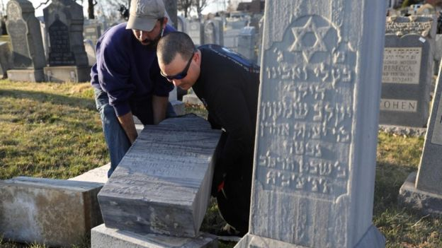 Scott Shandler (L) and Jon Lattanzio re-set a tombstone