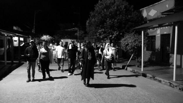 Animero y devotos caminando por las calles de Puerto Berrío.
