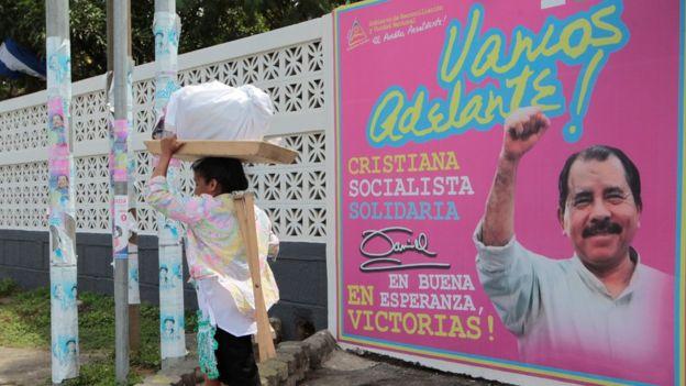 Una mujer pasa frente a un letrero de campaña de Daniel Ortega.