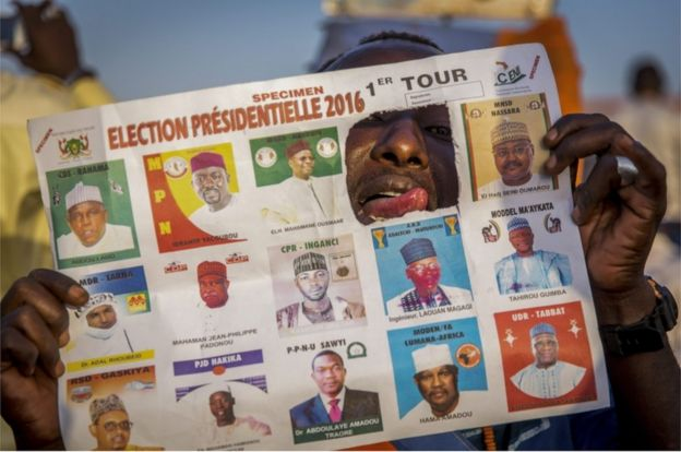 A photograph made available 20 February 2016 shows a supporter of main opposition candidate Hama Amadou who has ripped out the picture of incumbent president Issoufou Mahamadou in a specimen ballot paper during an election rally in Niamey, Niger 19 February 2016