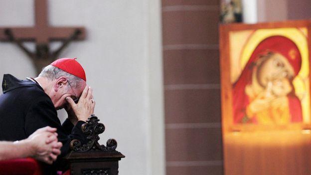 El cardenal Joachim Meisner, arrodillado y rezando.