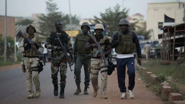 Malian soldiers walk in front of the Radisson hotel in Bamako (20 November 2015)