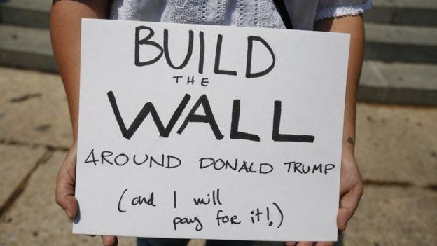 Em cartaz, manifestante defende construir um muro em volta de Donald Trump e diz que vai pagar por isso