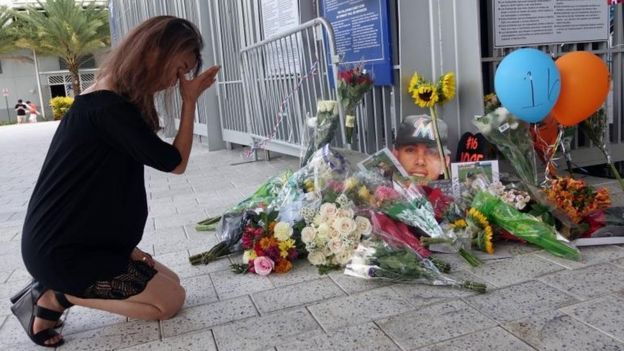 Una mujer llora frente al homenaje en Marlins Park.
