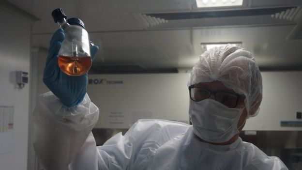 A scientist at INstituto D'Or holds up a bottle with liquid
