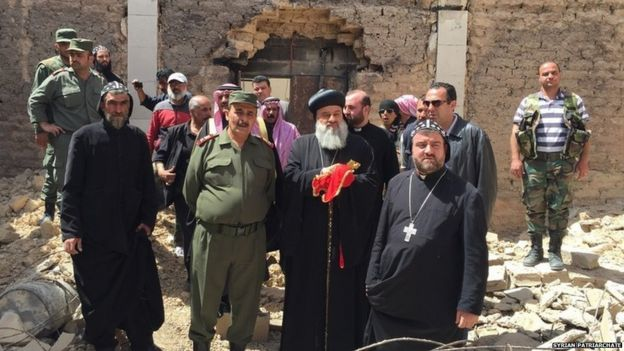 Patriarch Ignatius Aphrem II, the head of the Syrian Orthodox Church, (holding crucifix) visits al-Qaryatain on 8 April 2015