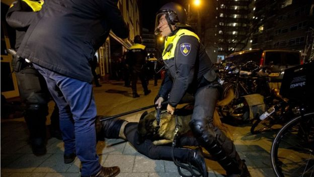 A police dog bites a demonstrator after riots break out at the Turkish consulate in Rotterdam, Netherlands, 12 March
