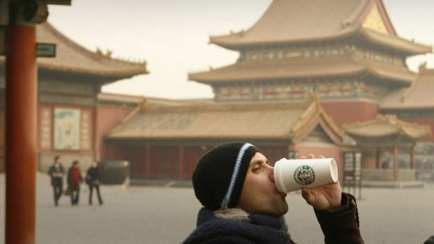 A man drinks a Starbucks coffee in Beijing's Forbidden City