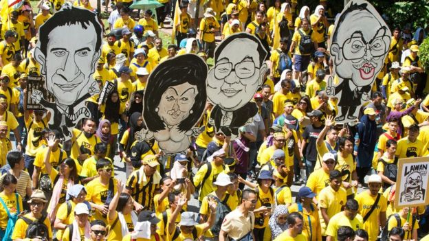 Protesters wearing yellow shirts in Kuala Lumpur hold up cartoons