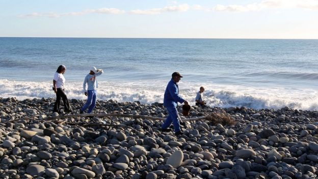 Volunteers search for more plane debris on the beach in Reunion. 31 July 2015