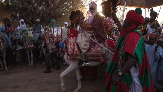 Emir passing through Kano on horseback
